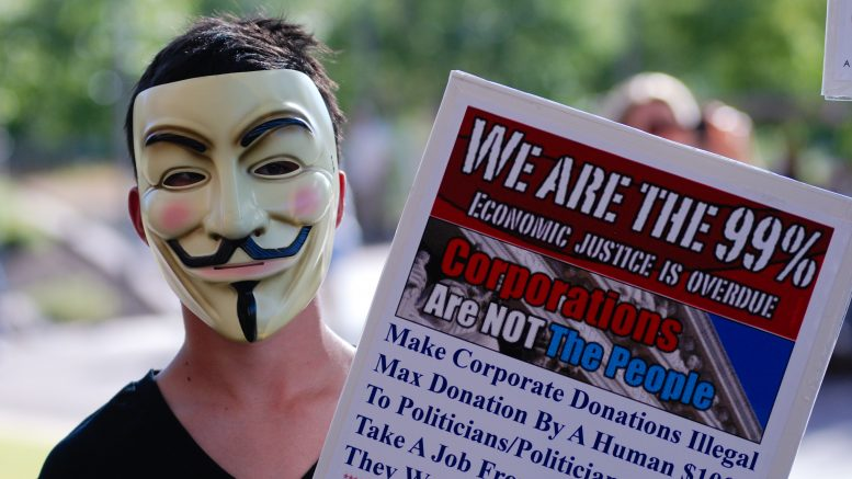 14 Oct 2011, Phoenix, Arizona, USA --- A man holding a sign and wearing a mask at the protest. -- People angry with banks and the United States government marched through downtown Phoenix in solidarity with those who have been demonstrating on Wall Street in New York City for the last month. USA. 14th October 2011 --- Image by © Parker Haeg / Demotix/Demotix/Corbis
