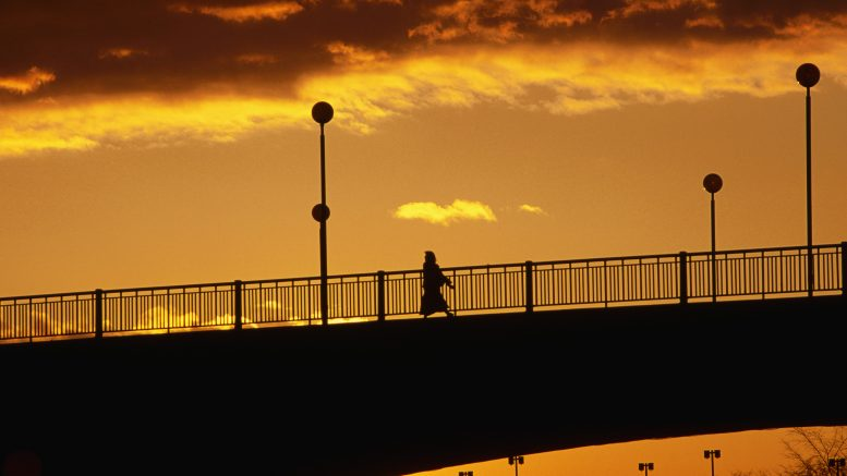 10 Nov 1994, Canada --- A pedestrian is silhouetted by golden skies during a sunrise over Rideau Canal in Ottowa, Ontario, Canada. --- Image by © Paul A. Souders/CORBIS