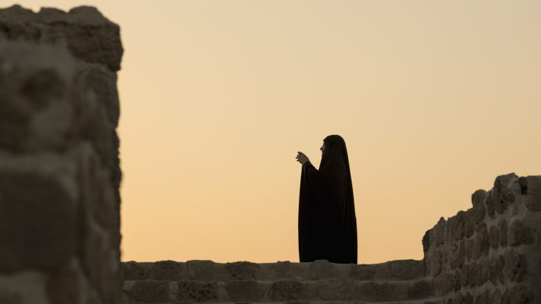 11 Dec 2014, Manama, Bahrain --- Muslim woman taking photo and silhouetted against sunset at Bahrain Fort near Manama at Seef, Bahrain --- Image by © Steve Heap/incamerastock/Corbis