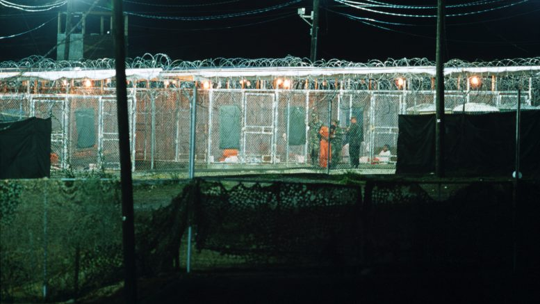 05 Apr 2002, Cuba --- Al Qaeda prisoners are guarded by the Marine guards at the Guantanamo Bay Naval Base. There are some 300 detainees being held at Camp X-ray. --- Image by © Brownie Harris/Corbis