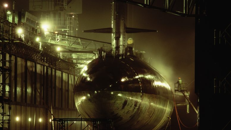ca. 1987, Groton, Connecticut, USA --- The hull of the USS Billfish gets a sandblasting in the huge floating drydock ship USS Shippingport, on a rainy night New London Submarine Base in Groton, Connecticut. --- Image by © Steve Kaufman/CORBIS