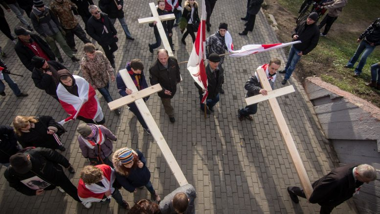 01 Nov 2015, Minsk, Belarus --- Minsk, Belarus. 1st November 2015 -- Belarus opposition supporters hold red and white flags and crosses at the annual Dzyady procession to the Kuropaty burial site on the outskirts of Minsk commemorating the victims of Stalin-era executions. -- Belarus opposition supporters held their annual procession of flags and wooden crosses to the Kuropaty burial site to pay tribute to the victims of mass Stalin-era executions on the outskirts of Minsk. --- Image by © Alyaksey Stalyarou/Demotix/Corbis