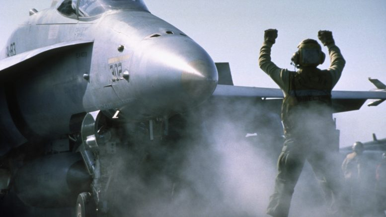 ca. February 1991 --- A flight deck crewman directs an F/A-18 Hornet aboard the USS Saratoga before take-off. The fighter jet is part of Strike Fighter Squadron 83 and Operation Desert Storm. --- Image by © CORBIS