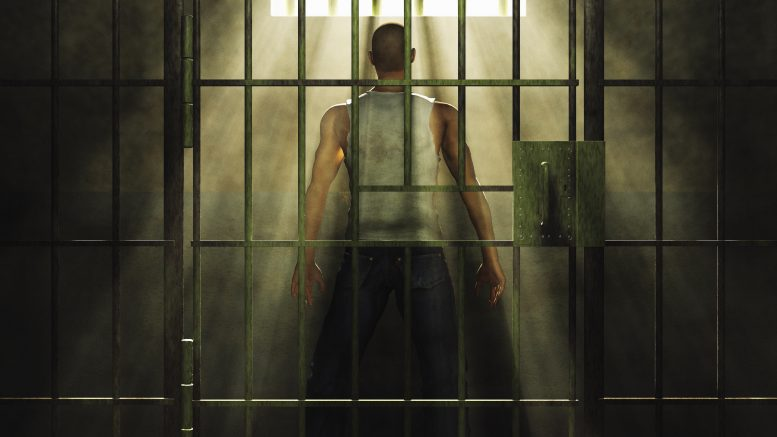 Light shining on man in prison cell --- Image by © Barry Downard/Ikon Images/Corbis