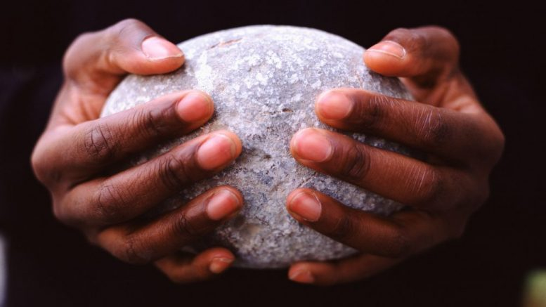 Man Holding Oval Stone --- Image by © Image Source/Corbis