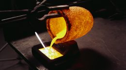 Molten gold pours into a bar mold from a red-hot crucible held by tongs. --- Image by © Charles O'Rear/Corbis