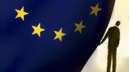 Businessman peeking behind European Union flag --- Image by © Gary Waters/Ikon Images/Corbis