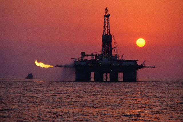 Oil Drilling Platform at Sunset --- Image by © Keith Wood/Corbis
